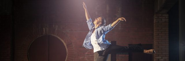A woman dancing in front of an urban background.