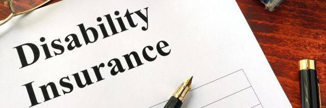 Disability insurance on a office table with a pen.