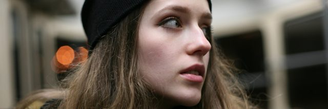 woman with long brown hair wearing a beanie and looking away on a train