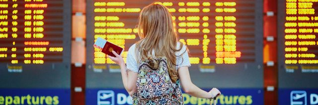 A woman standing in front of an airport departure board, while holding her suitcase, backpack, and passport.