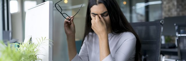 Woman with headache at office.