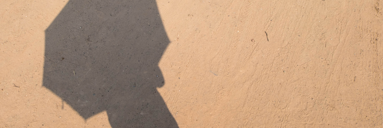 Shadow of someone holding an umbrella on the sand