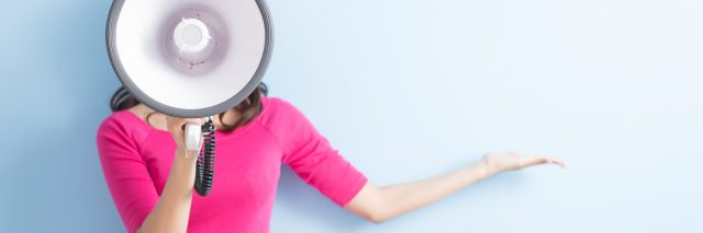 woman in a pink shirt holding up a megaphone