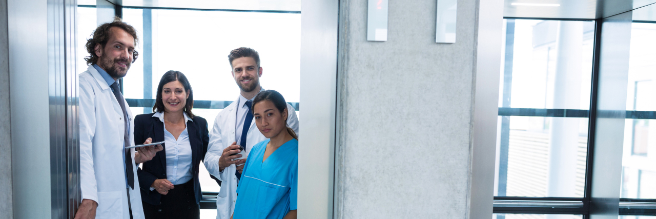 Doctors and businesswoman standing in elevator in hospital