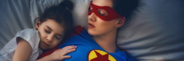 mother lying in bed with two small children sleeping on either side of her. the mom is wearing a superhero costume