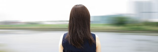 A woman looking at a blurred background.