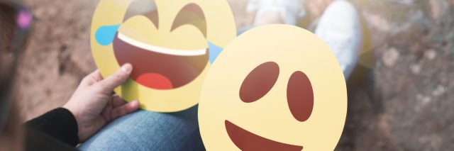 A woman holding cutouts of two emojis (one laughing, the other happy) on her lap.