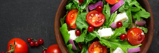 Fresh salad with arugula, feta cheese, red onion and red currant in a bowl.