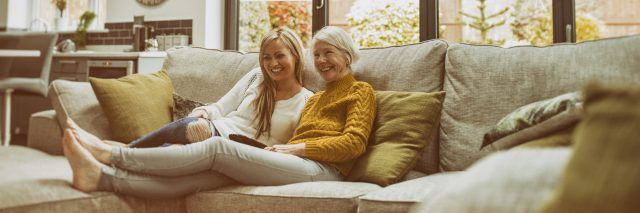 Mother and daughter watching television together on the sofa at home.