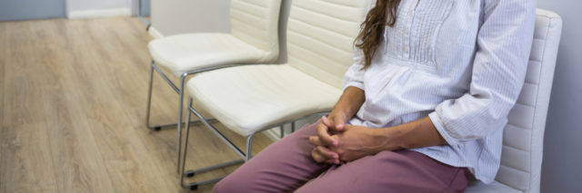 Sad patient sitting on chair in waiting room at hospital