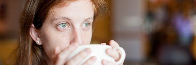A woman drinking out of a coffee mug.