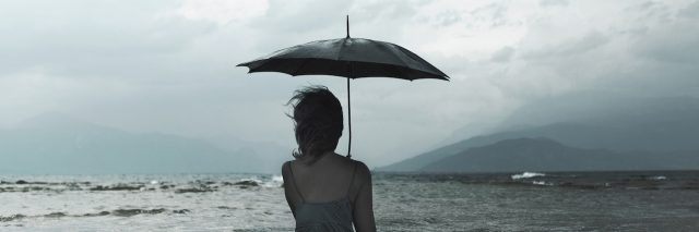 A woman holding an umbrella standing in the ocean