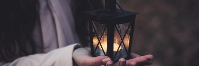 close up of woman holding tea light candle in in small lantern with both hands