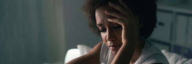 woman holding head looking sad