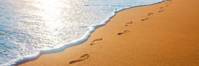 Beach, wave and footprints at sunset.