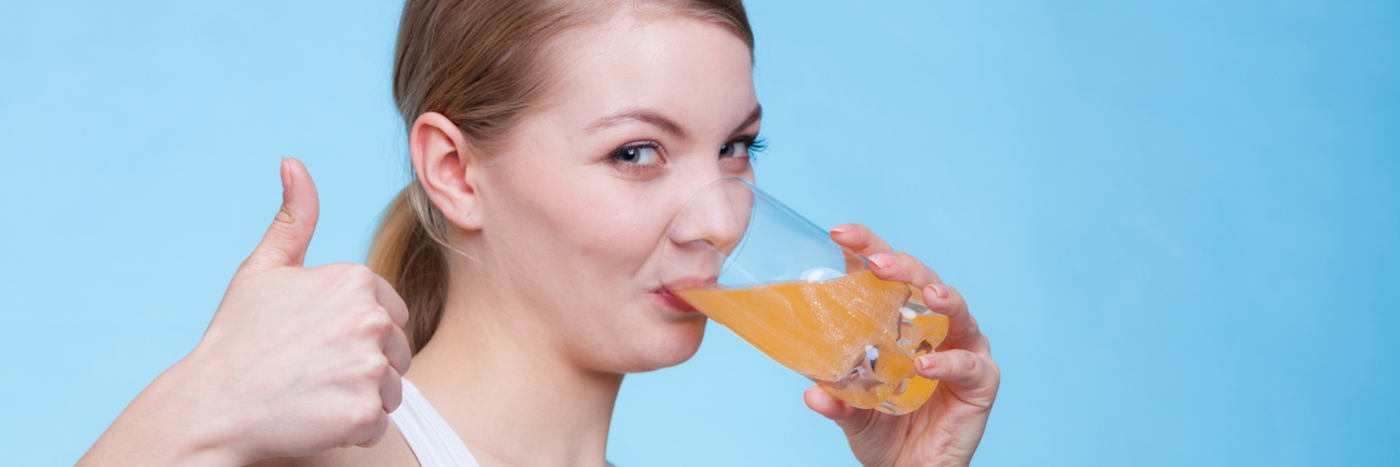 Food, health concept. Woman holding glass of orange flavored drink and drinking from it showing thumb up gesture. Studio shot on blue background