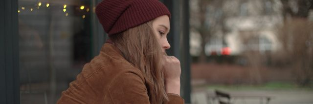 woman wearing a brown jacket and red beanie sitting outside at a cafe by herself
