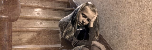 7 or 8 years old sad depressed and worried schoolgirl sitting on staircase desperate and scared suffering bullying and harassment at school in dramatic lighting and bullied children grunge edit