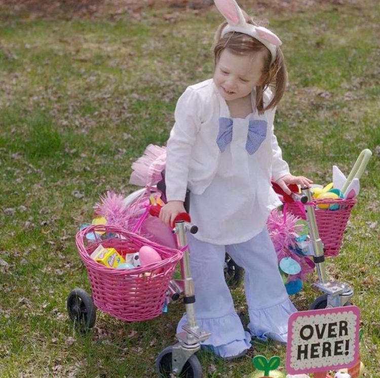 Little girls using walker, wearing bunny ears and two pink baskets and on the sides of the wakler