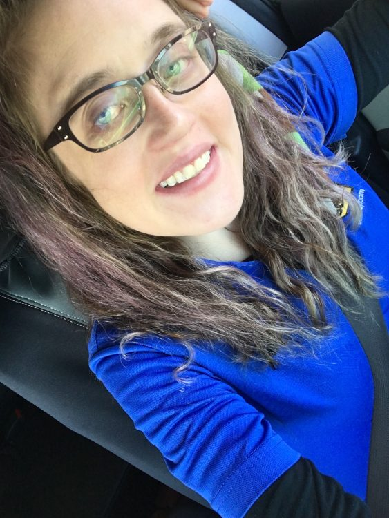 woman wearing a blue shirt and glasses and taking a selfie on her last day of work