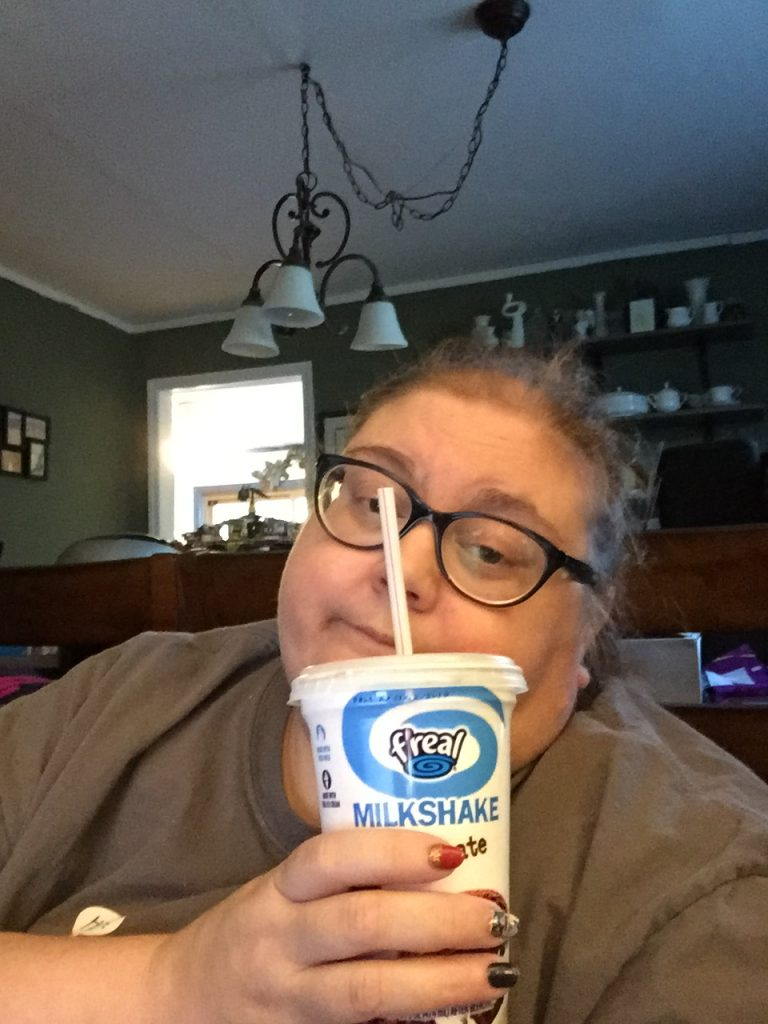 woman sitting in bed and drinking a milkshake