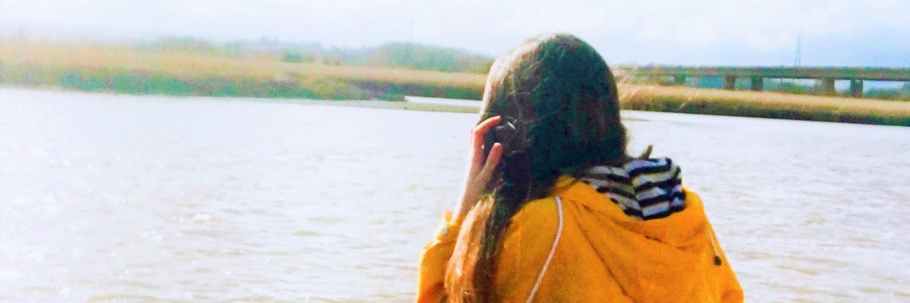 A woman looking at a body of water.