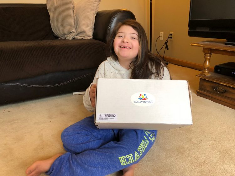 Girl with Down syndrome holding an EarlyVention box smiling