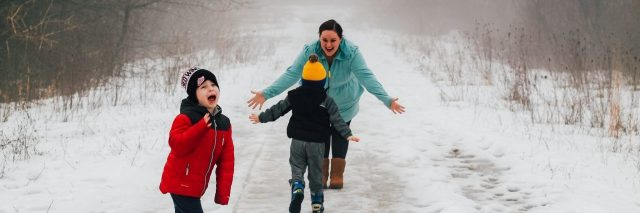 boys playing in the snow with mom