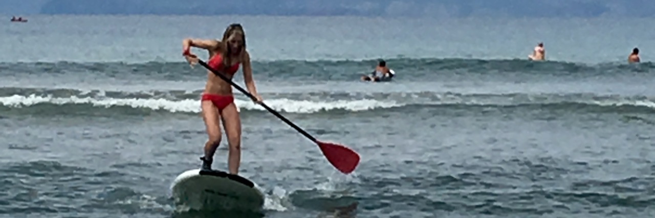 woman paddleboarding through waves in the ocean