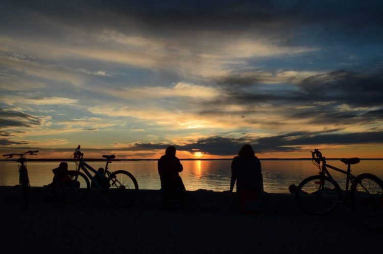 silhouette of friends and their bikes sitting on the beach watching a sunset over the ocean