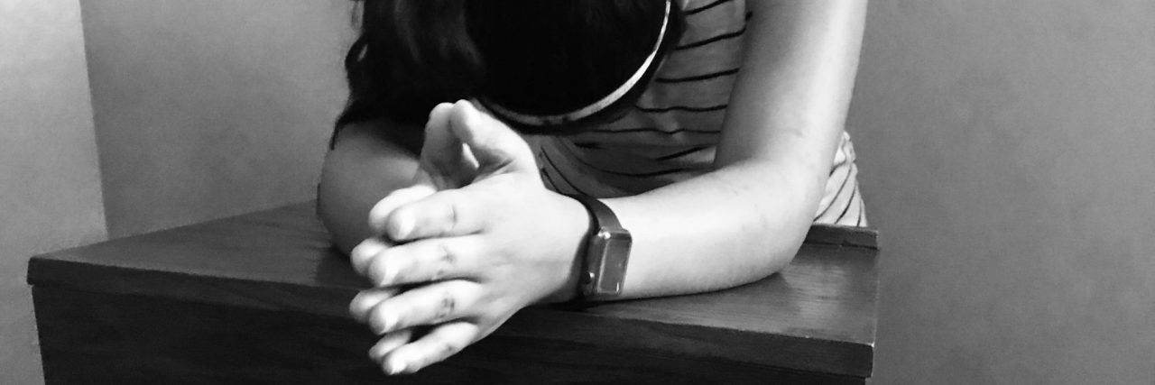 black and white photo of woman leaning on desk praying