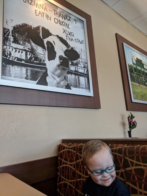 Little boy with down syndrome and cow poster above
