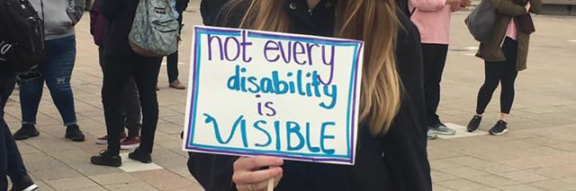 "Zoie stands in the center of the UIC quad, pavement under her feet. In the background is one building and several individuals engaged in conversations. She is wearing a black jacket, her blonde hair is just beyond her shoulders, and she is white. In her right hand, she holds a white sign with blue border that says ""not every disability is visible."""