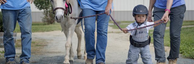 "Adorable toddler with Down syndrome ""walking"" horse with two adults."