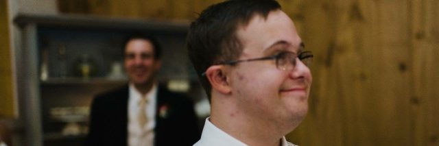 Young man with Down syndrome dressed up at wedding holding plate with slice of cake