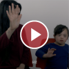 A mom and daughter waving with a red play button overlay