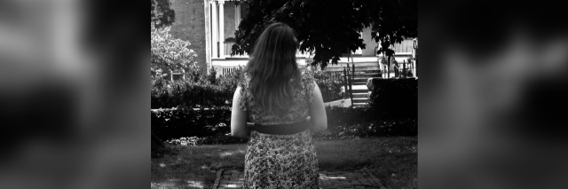 black and white photo of a woman in a dress walking outside