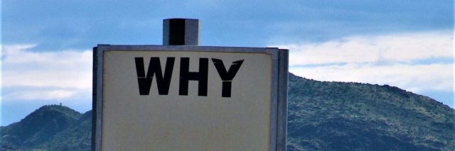 """a large white sign that says """"why?"""" in the middle of a field with a mountain in the background"""