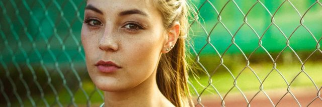 a woman with a ponytail standing in front of a fence