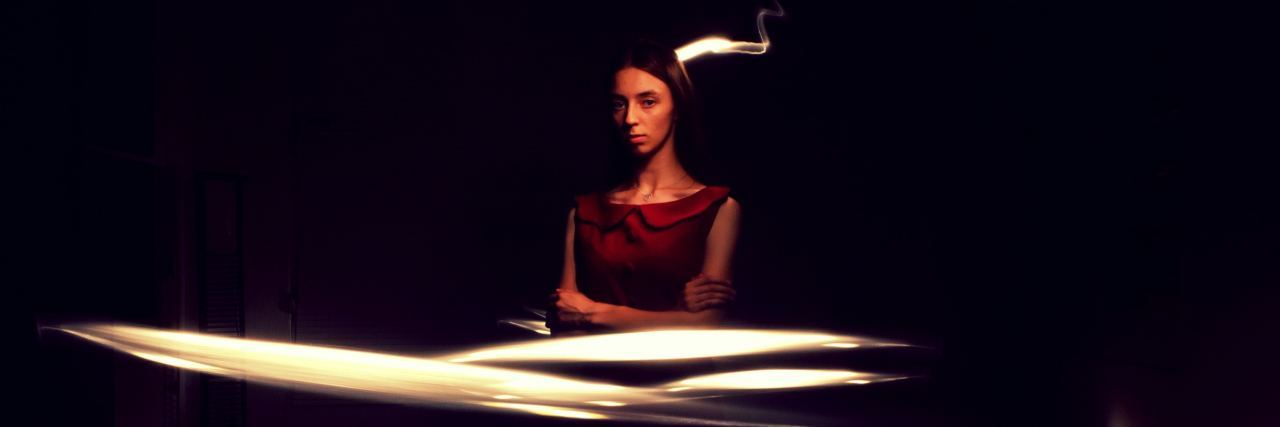 woman in dark room with lights swirling around her