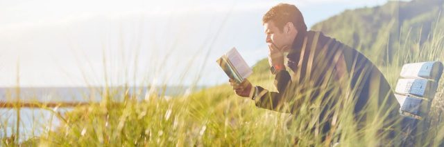 Man sitting by sea on bench near tall grass reading a book