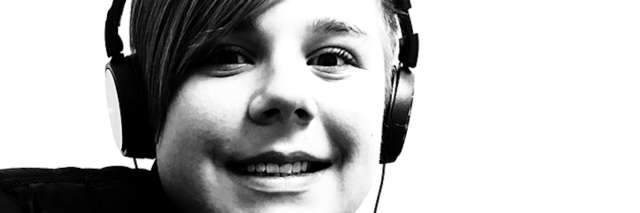 Black and white image of close up face boy wearing headphones smiling at camera