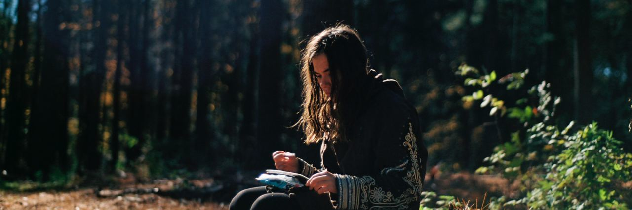 girl in the woods looking at a notebook