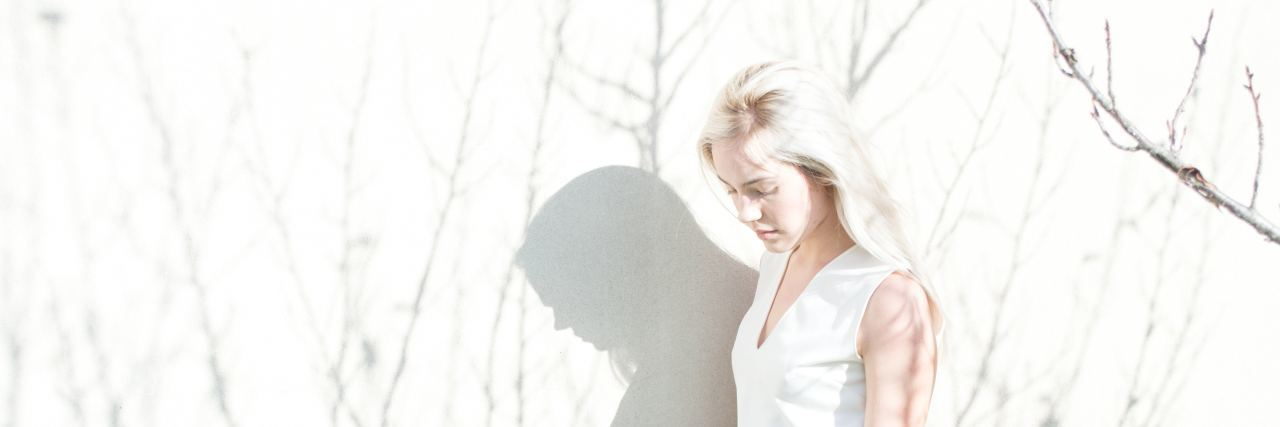 a woman with blonde hair stands outside with shadows of trees surrounding her
