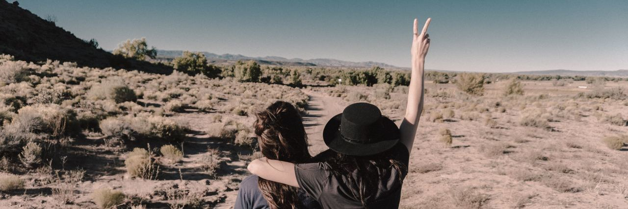 two women in the desert, one woman holding up the peace sign