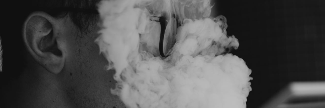 A man with smoke in his face.
