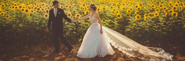newly married couple in front of field of sunflowers