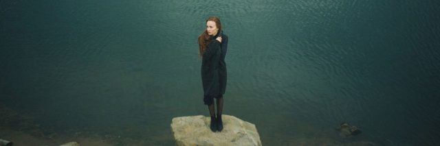 woman stands on rock surrounded by water