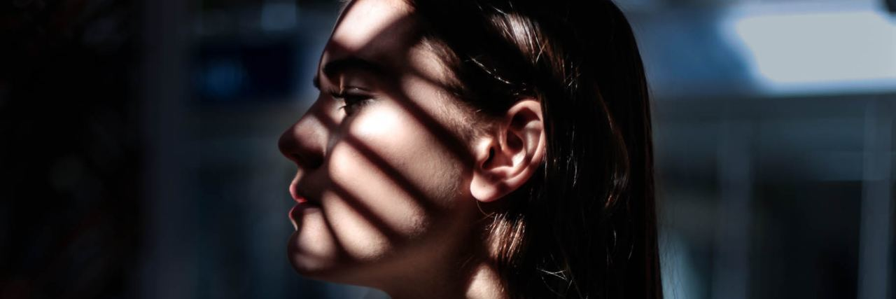 woman looking out window with shadow of blinds on her face