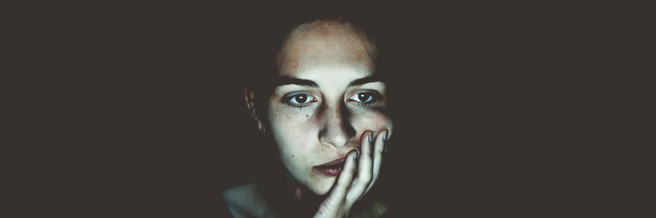 woman in the dark looking like she's contemplating